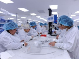 Lab technicians wearing white coats and blue hair covers assembling medical devices.
